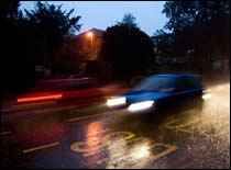 Photo of car on wet road.